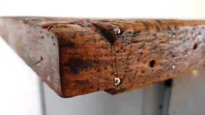 Werkbank aus Stahl und Holz. Nahaufnahme aus Perspektive der linken Tischplattenecke.